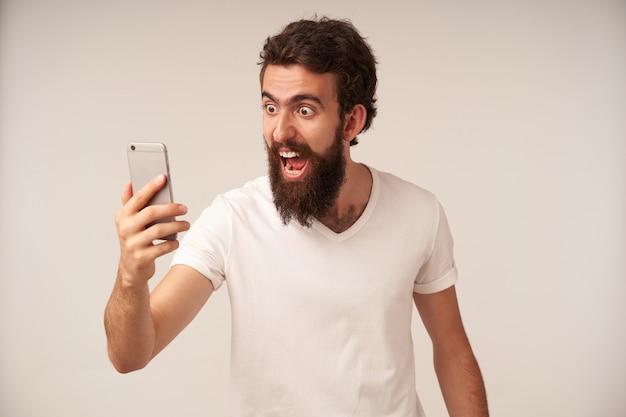 Zaskoczony brodaty mężczyzna patrzący na smartfona