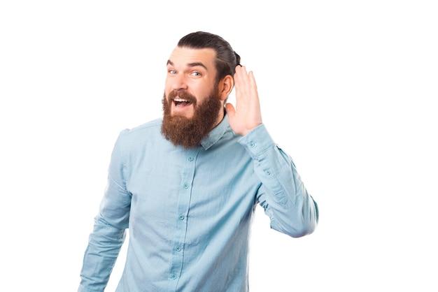 Zaskoczony brodaty mężczyzna robi gest usłyszeć na białym tle.