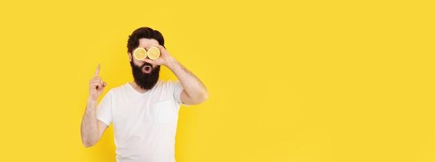 Zaskoczony brodaty mężczyzna trzyma plasterki cytryny przed oczami