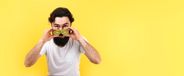 Zaskoczony, brodaty mężczyzna trzymający przed oczami plasterki zielonego kiwi w formie okularów