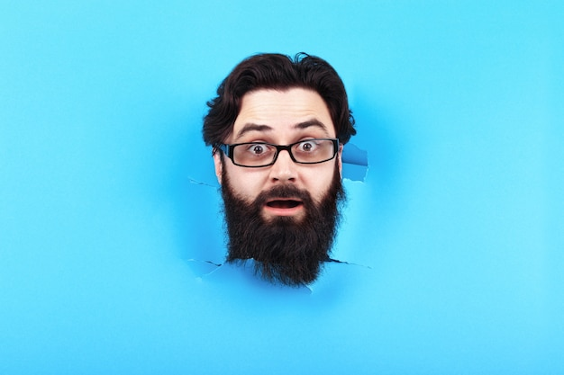 Zaskoczony brodaty mężczyzna w dziurze w niebieskiej ścianie