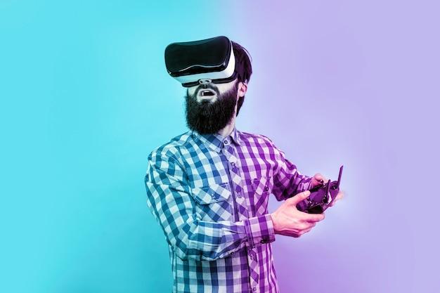 Zaskoczony brodaty mężczyzna w vr (okularach wirtualnej rzeczywistości) z pilotem w dłoni steruje dronem, stonowany obraz