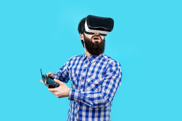 Zaskoczony brodaty mężczyzna w vr (okulary wirtualnej rzeczywistości) z pilotem w dłoni steruje dronem