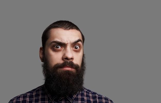 Zaskoczony brodaty mężczyzna z szeroko otwartymi oczami i dużymi wąsami.