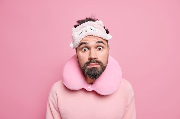 Zaskoczony, brodaty turysta mężczyzna nosi maskę na szyję na szyję, casualowy sweter, patrzy zszokowany