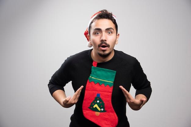 Zaskoczony brunet w czapce świętego mikołaja pokazujący świąteczną skarpetę.