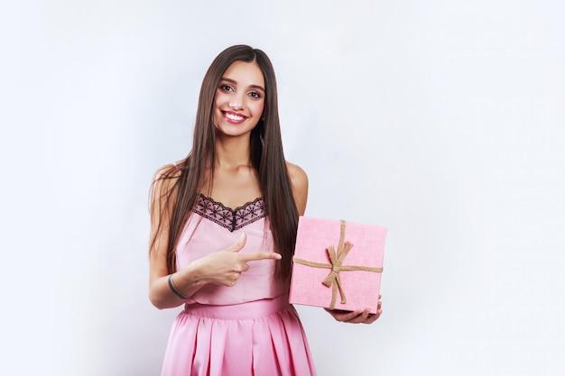 Zaskoczony brunetka dama gospodarstwa różowy prezent i patrząc