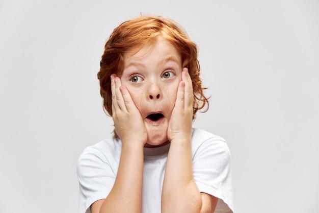 Zaskoczony chłopak trzymając się za twarz z otwartymi ustami patrzy w bok