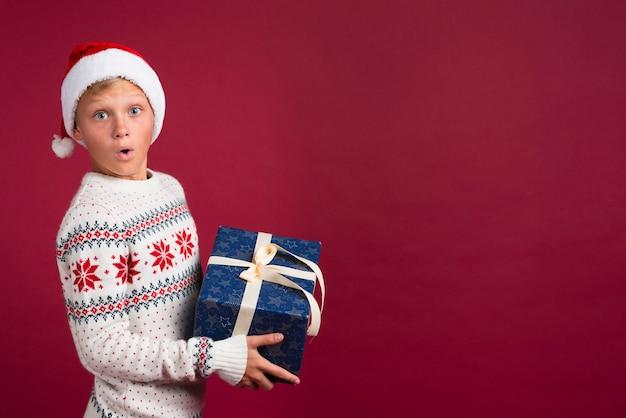 Zaskoczony chłopak z prezentem