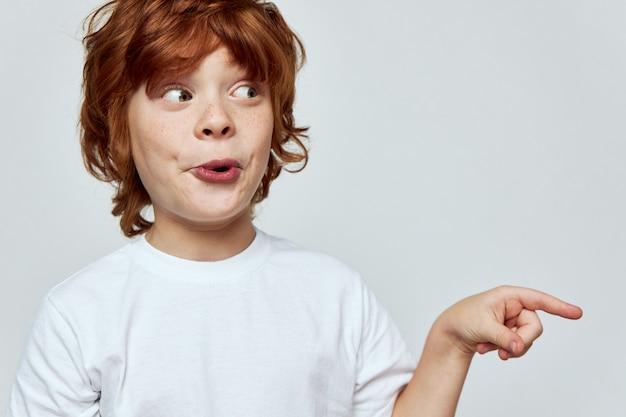 Zaskoczony chłopiec patrząc z boku pokazano palec szare tło przycięty widok kopiuj miejsce