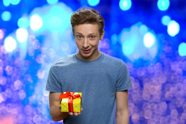 Zaskoczony chłopiec trzyma małe żółte pudełko na prezent
