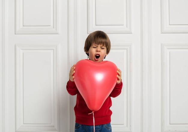 Zaskoczony chłopiec trzymając serce czerwony balon na białym tle