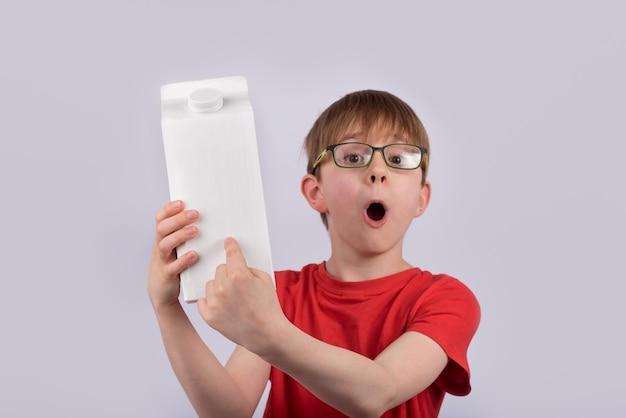 Zaskoczony chłopiec trzymający karton mleka lub soku i wskazujący na opakowanie. zawartość żywności składniki.