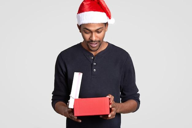 Zaskoczony ciekawy mężczyzna święty mikołaj nosi świąteczny kapelusz