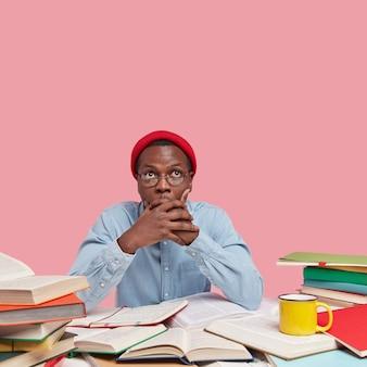 Zaskoczony ciemnoskóry mężczyzna zakrywa usta obiema rękami, stara się być oniemiały, skupiony w górę, nosi czerwoną czapkę i koszulę, pozuje na biurku