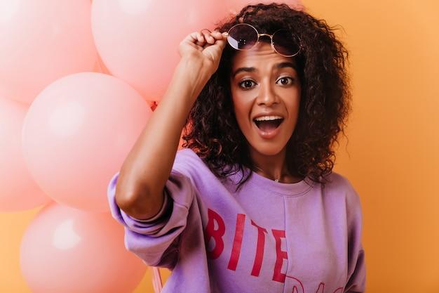 Zaskoczony czarny urodziny dziewczyna dotyka jej okularów. emocjonalna dama kręcone pozuje z balonów na imprezę.
