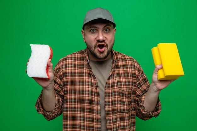 Zaskoczony czystszy mężczyzna trzymający gąbki