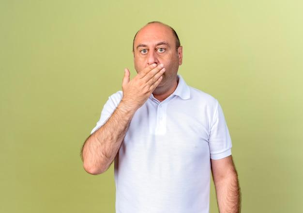 Zaskoczony dojrzały mężczyzna zakrył usta ręką odizolowaną na oliwkowej ścianie