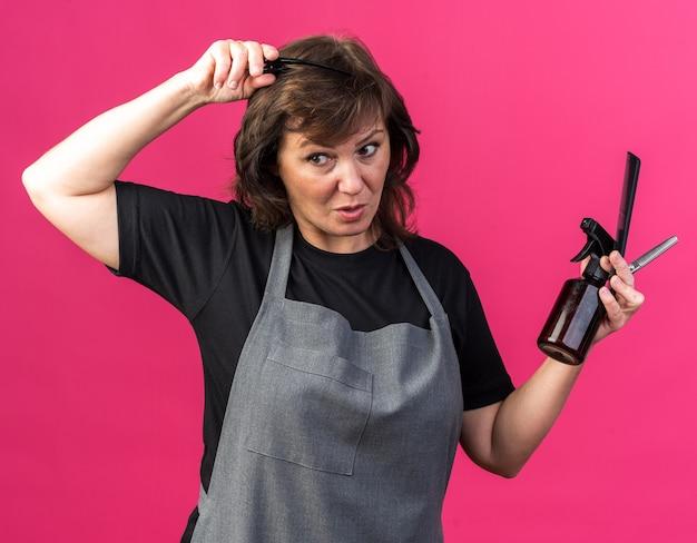 Zaskoczony dorosły kaukaski fryzjer żeński w mundurze trzymającym narzędzia fryzjerskie na białym tle na różowym tle z miejscem na kopię