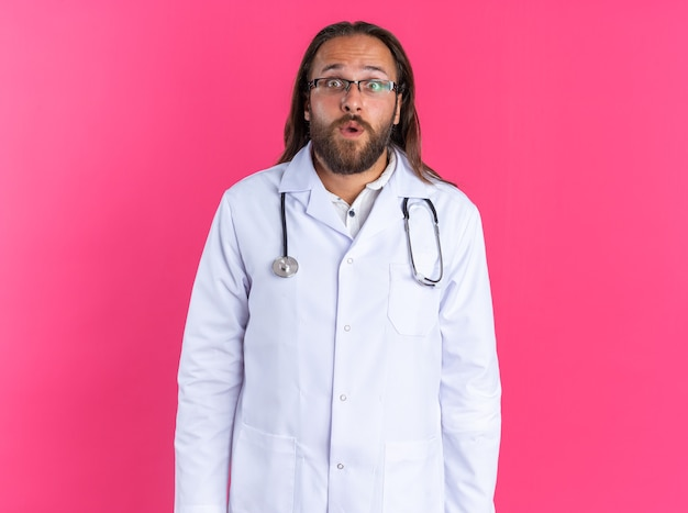 Zaskoczony dorosły lekarz mężczyzna ubrany w szatę medyczną i stetoskop w okularach, patrzący na kamerę odizolowaną na różowej ścianie