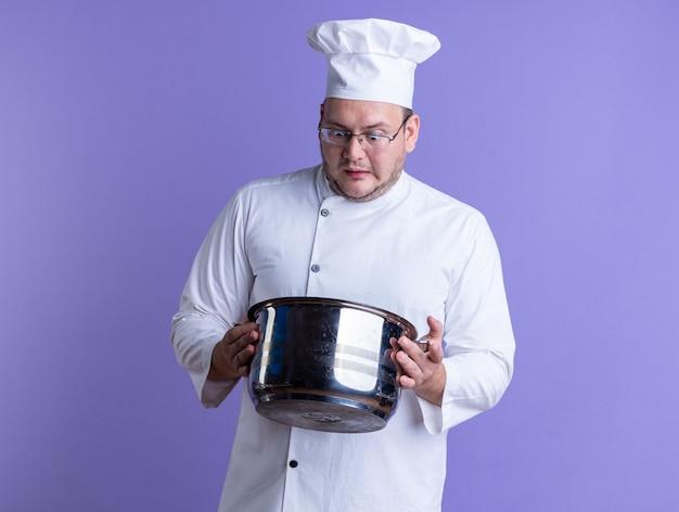 Zaskoczony dorosły mężczyzna kucharz w mundurze szefa kuchni i okularach trzymający garnek, zaglądający do środka, odizolowany na fioletowej ścianie z miejscem na kopię