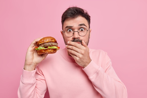Zaskoczony dorosły mężczyzna trzyma pysznego burgera