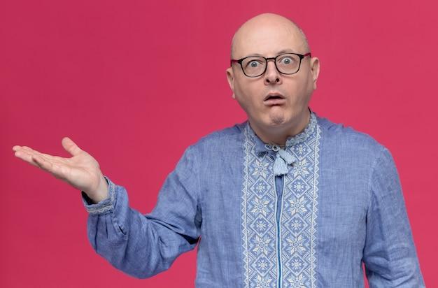 Zaskoczony dorosły mężczyzna w niebieskiej koszuli w okularach wskazujących na bok ręką