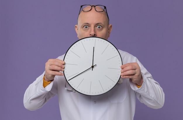 Zaskoczony dorosły mężczyzna w okularach w mundurze lekarza ze stetoskopem trzymającym zegar