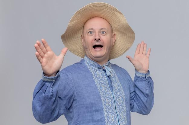 Zaskoczony dorosły mężczyzna w słomkowym kapeluszu i niebieskiej koszuli stojący z uniesionymi rękami
