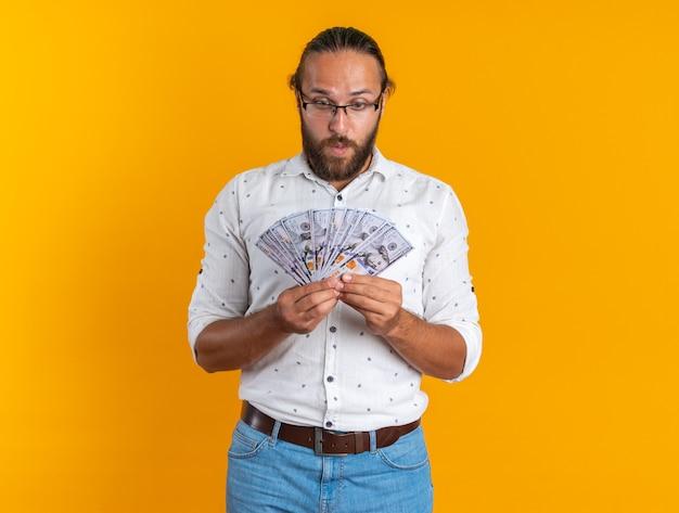 Zaskoczony dorosły przystojny mężczyzna w okularach trzymający i patrzący na pieniądze izolowane na pomarańczowej ścianie z miejscem na kopię
