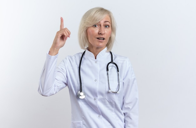 Zaskoczony dorosły słowiański lekarka w szacie medycznej ze stetoskopem skierowanym w górę na białym tle na białym tle z miejsca na kopię