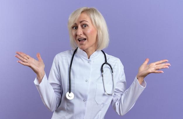 Zaskoczony dorosły słowiański lekarka w szacie medycznej ze stetoskopem, trzymając ręce otwarte na białym tle na fioletowym tle z miejscem na kopię