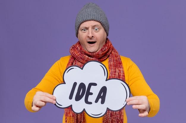 Zaskoczony dorosły słowiański mężczyzna w czapce zimowej i szaliku na szyi, trzymający i patrzący na bańkę pomysłów
