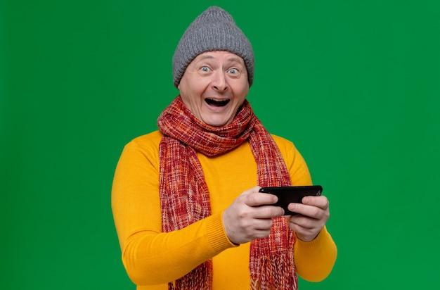 Zaskoczony dorosły słowiański mężczyzna w czapce zimowej i szaliku na szyi, trzymający telefon