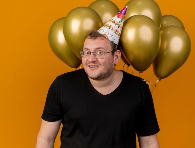 Zaskoczony dorosły słowiański mężczyzna w okularach optycznych w czapce urodzinowej stoi przed balonami z helem