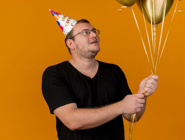 Zaskoczony dorosły słowiański mężczyzna w okularach optycznych w czapce urodzinowej trzyma i patrzy na balony z helem