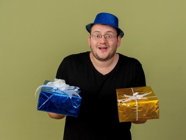 Zaskoczony dorosły słowiański mężczyzna w okularach optycznych w niebieskiej imprezowej czapce trzyma pudełka na prezenty