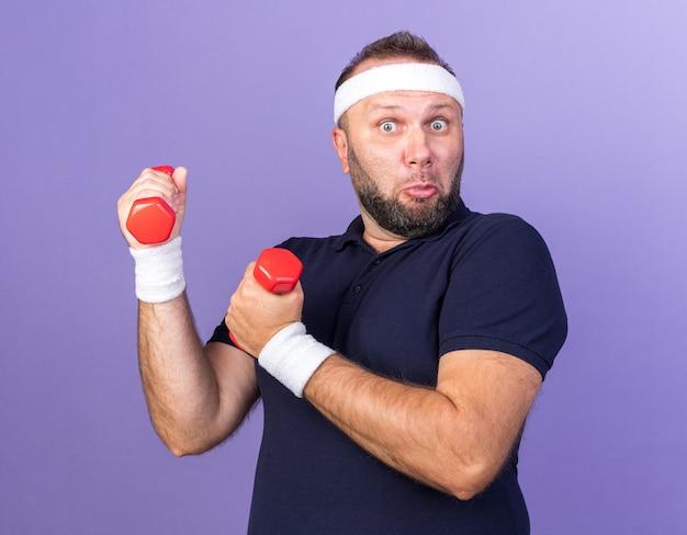 Zaskoczony dorosły słowiański sportowy mężczyzna noszący opaskę i opaski na nadgarstki trzymający hantle izolowane na fioletowej ścianie z kopią przestrzeni