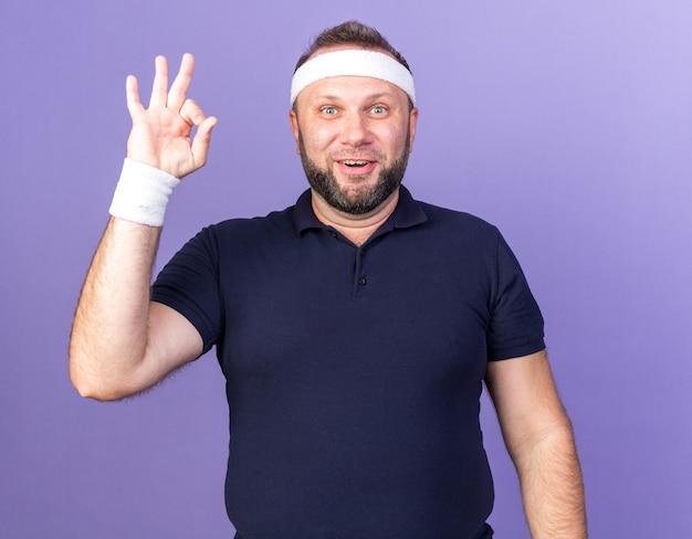 Zaskoczony dorosły słowiański sportowy mężczyzna noszący opaskę i opaski na rękę, wskazujący na znak ok na fioletowej ścianie z miejsca na kopię