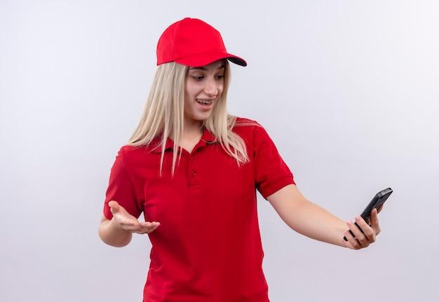 Zaskoczony dostawy młoda dziewczyna ubrana w czerwoną koszulkę i czapkę patrząc na telefon na jej dłoni na na białym tle