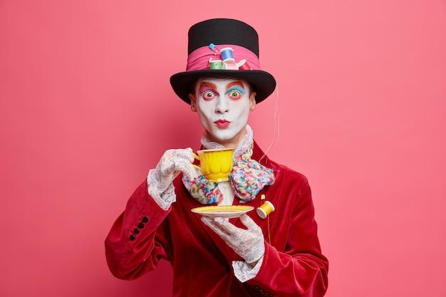 Zaskoczony dżentelmen ma wizerunek postaci z krainy czarów, nosi arystokratyczny kostium, koronkowe rękawiczki, kapelusz i pije, herbata ma kolorowy makijaż czaszki na różowej ścianie