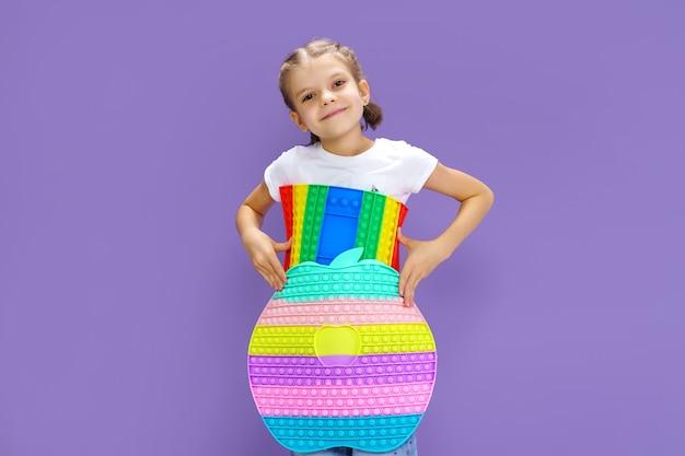 Zaskoczony dzieciak trzymający ogromne jabłko antystresowe bańki umiejętności motoryczne pop to zabawne dziecko trzymające kolor pop...