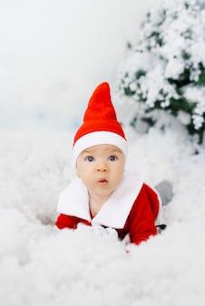 Zaskoczony dzieciak w małym stroju świętego mikołaja na sztucznym śniegu. święta bożego narodzenia, rabaty i wyprzedaże