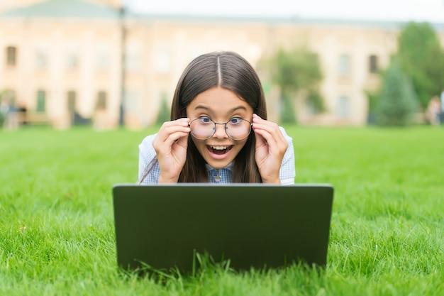 Zaskoczony dzieciak w okularach, grający w grę online na laptopie, relaksujący się na zielonej trawie w parku
