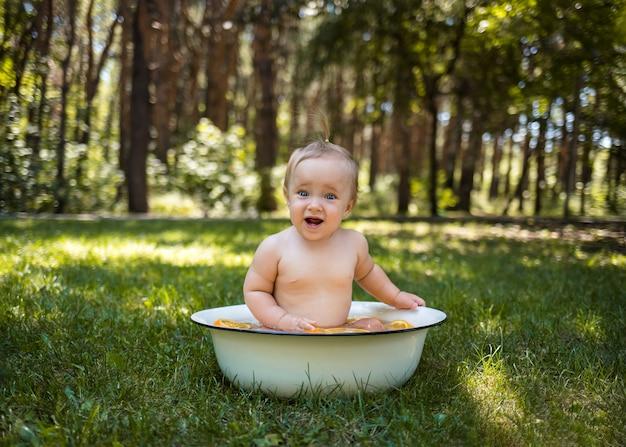Zaskoczony dziecko siedzi w białej misce z wodą i pomarańczami w naturze