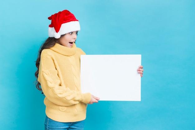 Zaskoczony dziewczyna z makieta plakat w ręce