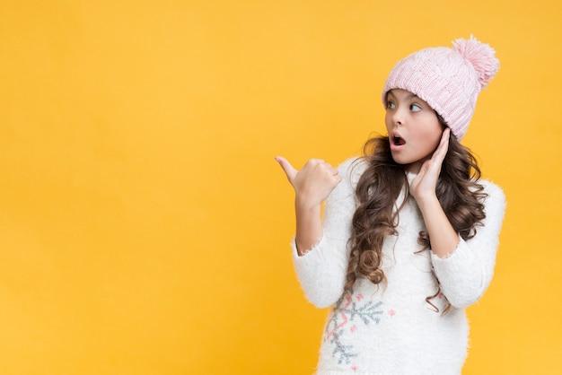 Zaskoczony dziewczynka nosi ubrania zimowe