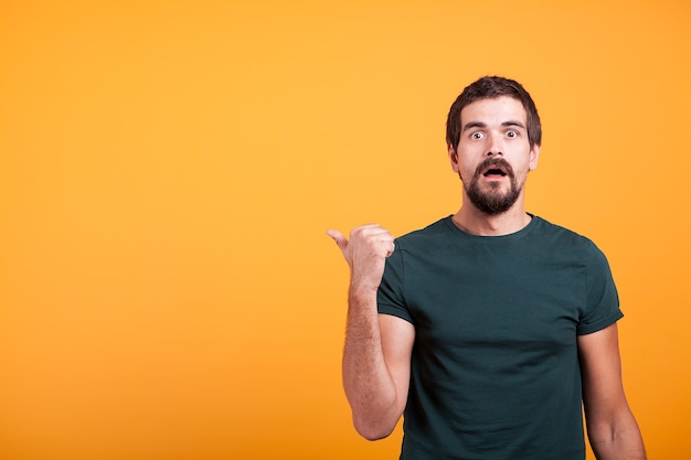 Zaskoczony emocjonalny dorosły mężczyzna, wskazując na copyspace, które jest dostępne dla twojego tekstu, reklamy lub promocji. koncepcja zdumienia i entuzjazmu