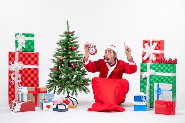 Zaskoczony emocjonalny święty mikołaj siedzi na ziemi i pokazuje zegar w pobliżu prezentów i udekorowane choinki na białym tle