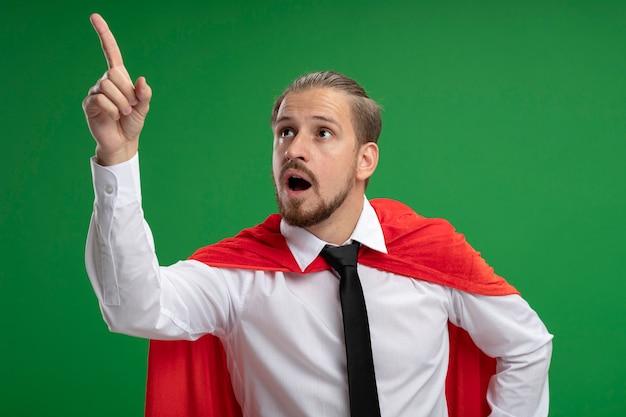Zaskoczony facet młody superbohater sobie punkty krawata z boku na białym tle na zielonym tle